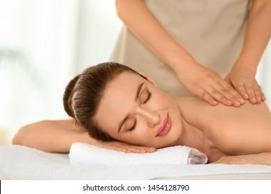 Beautiful young woman enjoying massage in spa salon