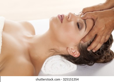 beautiful young woman enjoying a massage of the forehead