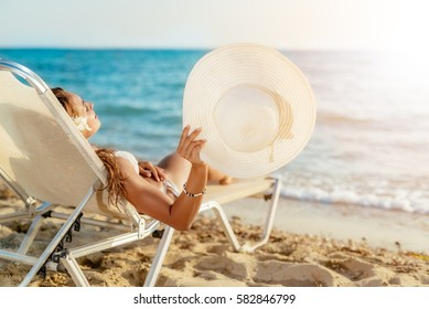 Beautiful young woman enjoying on the beach. She is lying on sunbed, holding summer hat and sunbathing.