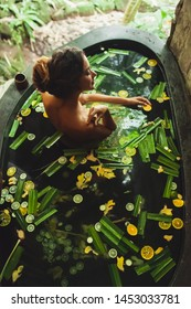 Beautiful young woman enjoying in outdoor spa. Luxury stone bath tub with jungle view. Natural organic tropical ingredients in the water: ginger, lime, orange and sea salt. Beauty treatment concept.
