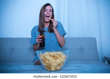 A beautiful young woman enjoying program on a screen alone at home and eating potato chips