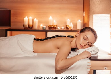 Beautiful young woman enjoying relaxing treatments the stone therapy at the spa salon by candlelight. The concept of relaxing and rejuvenating procedures
