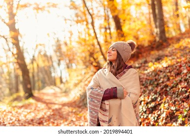 Beautiful young woman enjoying sunny autumn day in nature, walking down the forest path covered with colorful fallen leaves and relaxing, taking a breath of fresh air