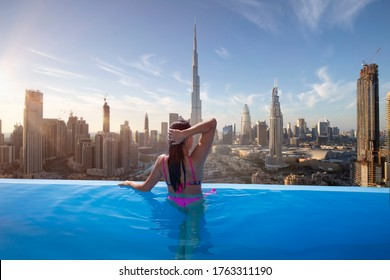 Beautiful young woman enjoys the panoramic view from an infinity pool on downtown Dubai - Shutterstock ID 1763311190