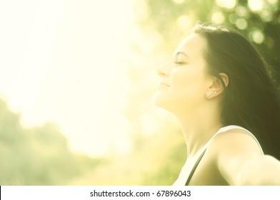 Beautiful young woman enjoys sun beams at summer park. Low contrast.