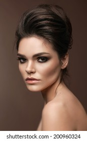 Beautiful young woman with evening make-up and volume hairstyle . Smoky eyes. Fashion photo
