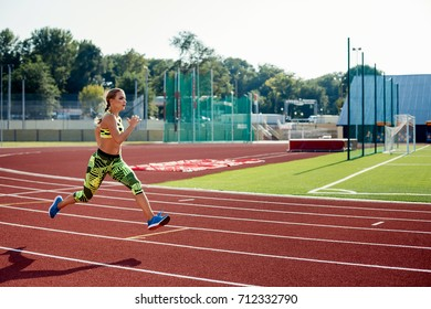 Beautiful young woman exercise jogging and running on athletic track on stadium.