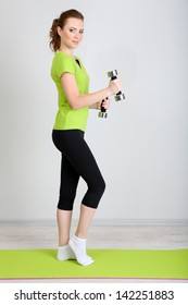 Beautiful young woman exercises with dumbbell