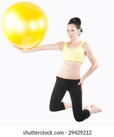 beautiful young woman exercising with yellow ball