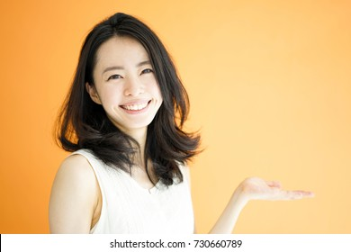 Beautiful young woman explaining against orange background