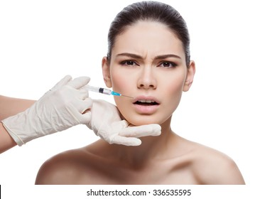 Beautiful young woman with expression of pain on face gets injection in lips from sergeant. Isolated over white background.