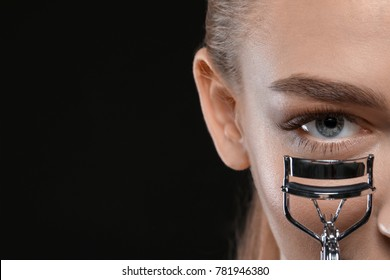 Beautiful young woman with eyelash curler on black background, closeup