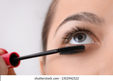 Beautiful young woman with eyelash extensions applying mascara on light background, closeup