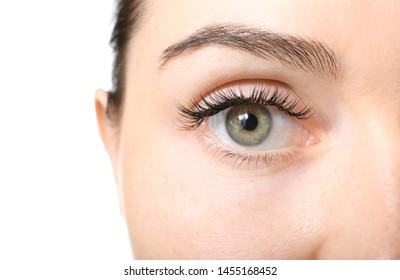 Beautiful young woman with eyelash extensions on white background, closeup