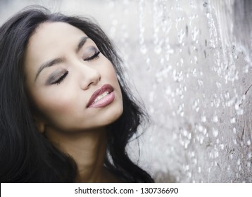 Beautiful young woman with eyes closed as water splashes