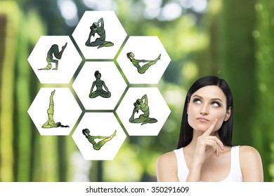 Beautiful young woman with eyes raised up hand to the chin dreaming about taking up sport exercise, yoga, illustrations of several exercises near her, green background, concept of healthy life