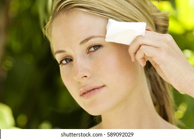 Beautiful young woman with face wipe