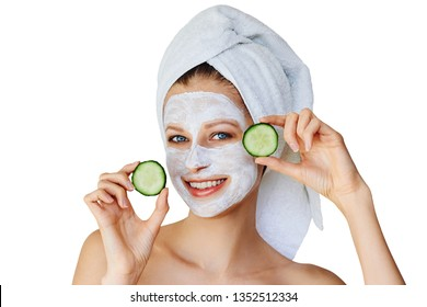 Beautiful young woman with facial mask on her face holding slices of fresh cucumber. Skin care and treatment, spa, natural beauty and cosmetology concept. Isolated over white background