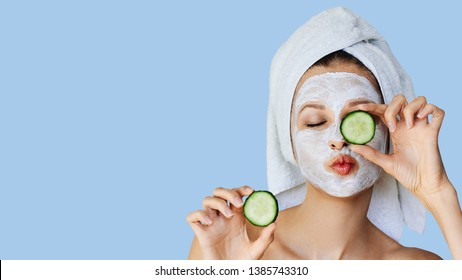 Beautiful young woman with facial mask on her face holding slices of fresh cucumber. Skin care and treatment, spa, natural beauty and cosmetology concept, over blue background with copy space