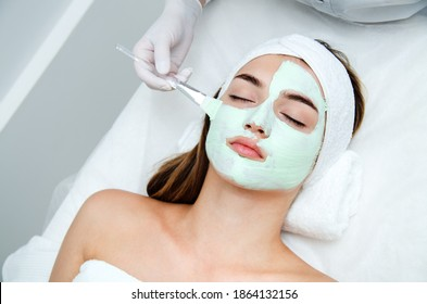 Beautiful young woman with facial mask in beauty salon. Girl getting beauty treatment facial care by beautician at spa salon.