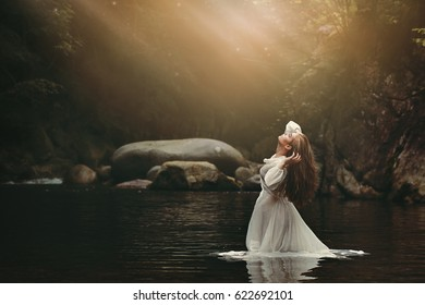Beautiful young woman in fairy pond. Dark fantasy