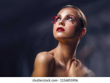 Beautiful young woman with fashion red makeup against a dark background. Female look up