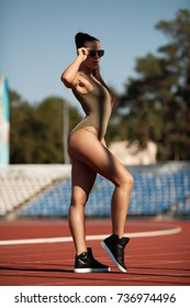 Beautiful young woman in fashionable bodysuit outdoor. Sexy fit woman on stadium.