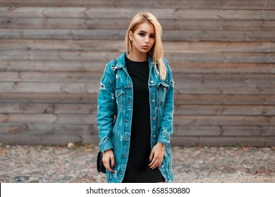 Beautiful young woman in fashionable denim jacket posing near vintage wooden wall