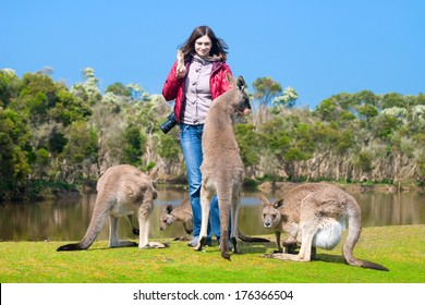 Beautiful young woman feeding kangaroos in Phillip Island Wildlife Park, Australia