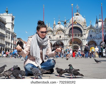 Beautiful young woman feeding pigeons on the Piazza San Marco