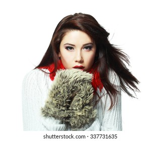 beautiful young woman feeling cold wind in winter hearing warm closthes and fur gloves isolated over white