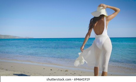Beautiful young woman, feeling happy, standing with back, white swimsuit, white straw hat, in white shawl, background of sea blue water, sand. Concept: sun, travel, vacation, freedom, diet, rest, sea.