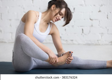 Beautiful young woman feeling pain in her foot during sport workout indoors, close-up,  focus on hands