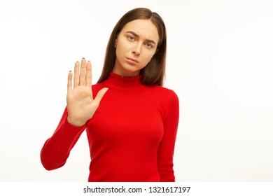 Beautiful young woman feels danger, stretches hand, holds palm in stop sign, prevents something bad, wears red sweater, model against white background.