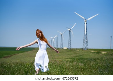 Beautiful young woman in a field against a background of windmills, summer.