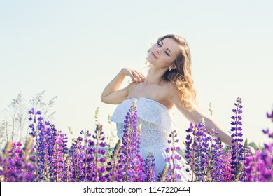 Beautiful young woman in a field with blooming lupines