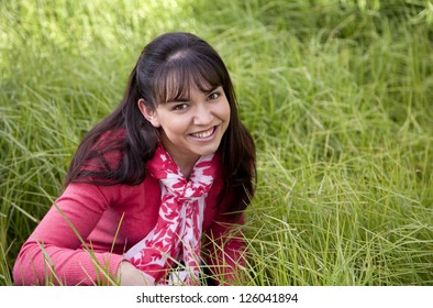 Beautiful young woman in a field of grass with copy space