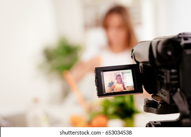 Beautiful young woman filming her blog broadcast about healthy food at the home. Selectiv focus. Focus on foreground, on camera.
