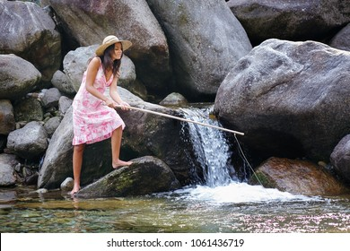 Beautiful young woman fishing in a river. Fun and relax in nature