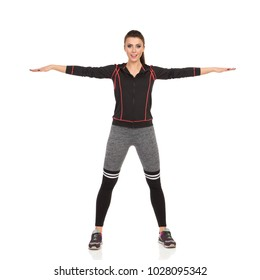 Beautiful young woman in fitness clothes is standing legs apart, holding arms outstretched, looking at camera and talking. Full length studio shot isolated on white.