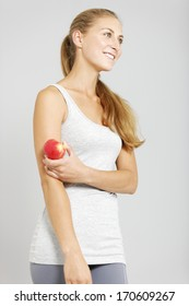 Beautiful young woman in fitness clothes holding an apple.