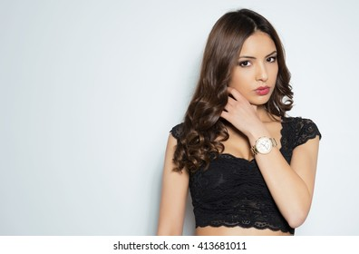 Beautiful young woman with flawless skin and perfect make-up wearing wrist watch