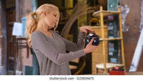 Beautiful young woman at the flea market looking at antique pot