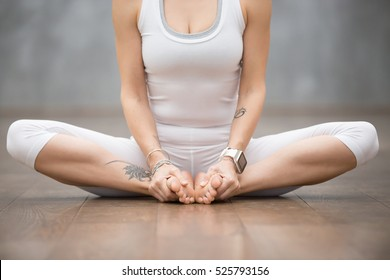 Beautiful young woman with floral tattoos working out against grey wall, doing yoga or pilates exercise, sitting in baddha konasana, bound angle, cobbler, butterfly pose. Close up shot