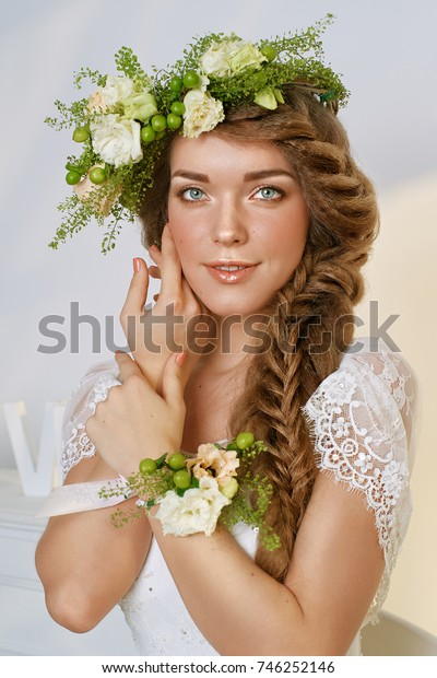 beautiful young woman with floral wreath on her head and long braided hair