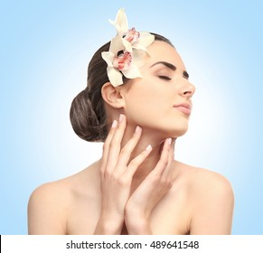 Beautiful young woman with flowers in hair on blue background. SPA concept.