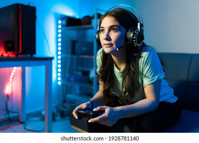 Beautiful young woman focusing on winning a video game with a remote controller. Female gamer enjoying a video game in a console during a leisure day in her bedroom