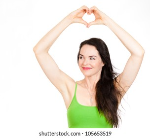A beautiful young woman forming a love heart with her hands over her head and looks at copyspace. Isolated on white