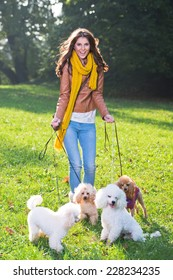 Beautiful young woman with four poodles in the park