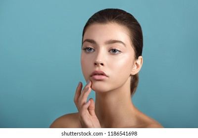 Beautiful young  woman with fresh clean perfect skin. Portrait of beauty model with natural make up and and hand with manicure touching face. Spa, skincare and wellness.
